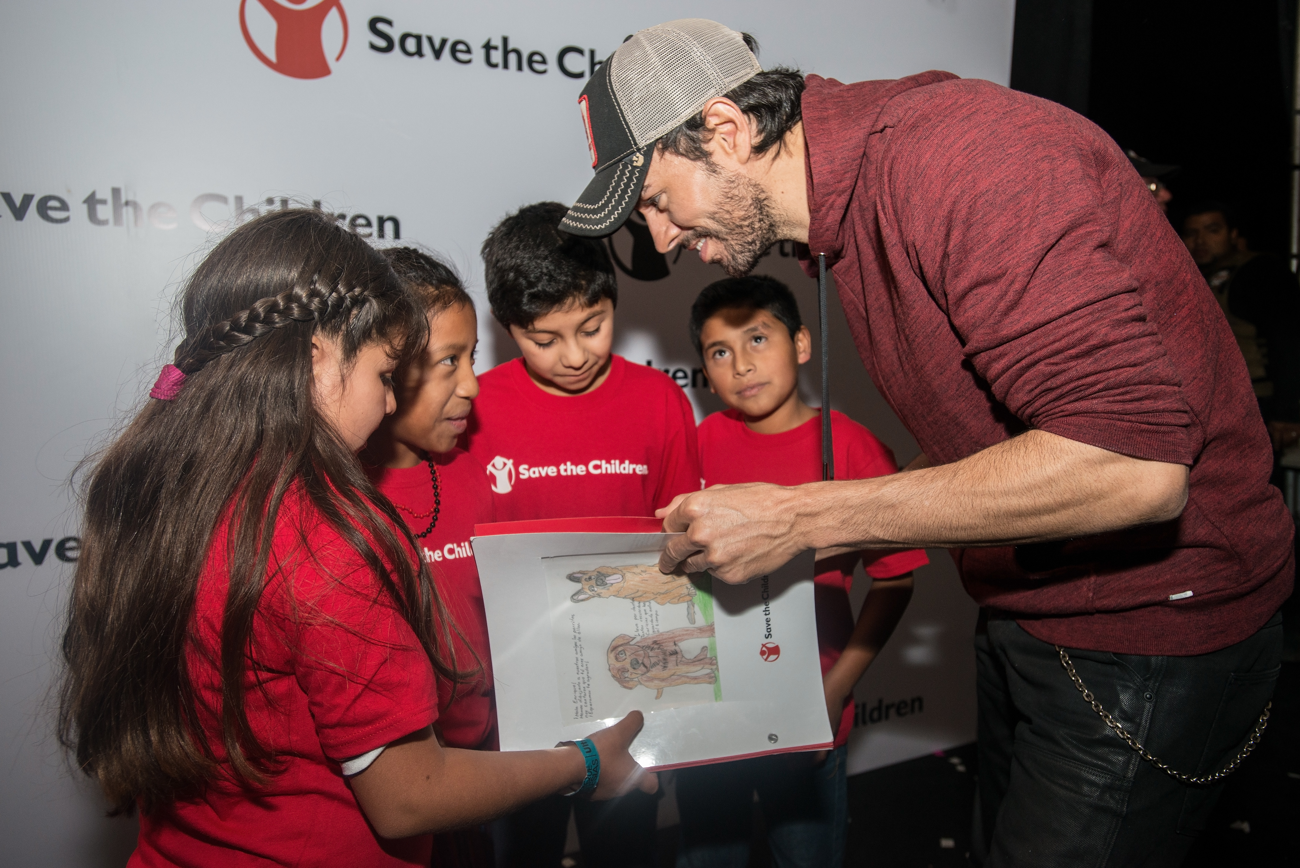 Photos are Embargoed until Tuesday December 13th, 2016: International pop star Enrique Iglesias talks with, from left, Henely, Juana, Gerson and Julio, before his Dec. 9, 2016, concert in Guatemala City, Guatemala. The kids, who all participate in Save the Children's Literacy Boost program in Guatemala, created a handmade book as a thank you gift for Iglesias, who, through a partnership with Microsoft, has donated $200,000 in software to Save the Children to strengthen its literacy programming for elementary school-age children in El Salvador, Guatemala and Peru.