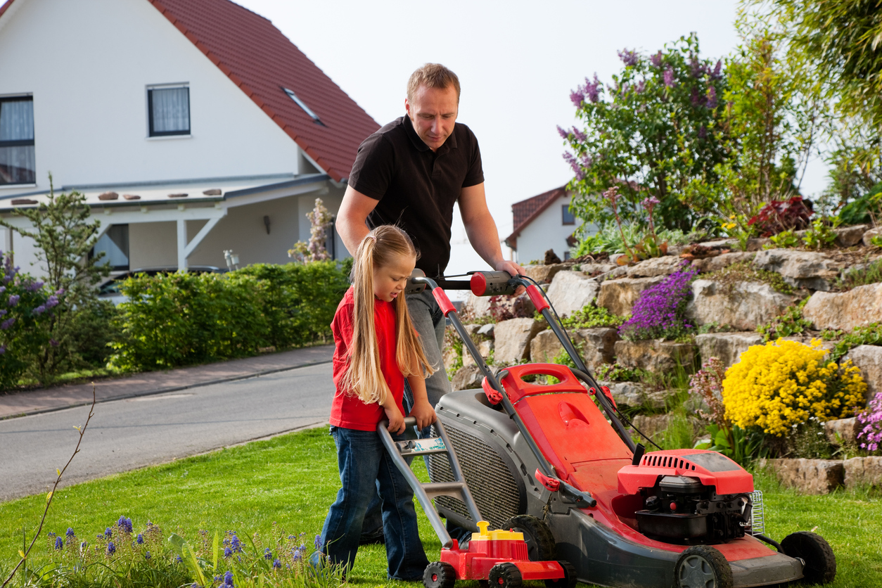 Father and Child mowing the lawn together