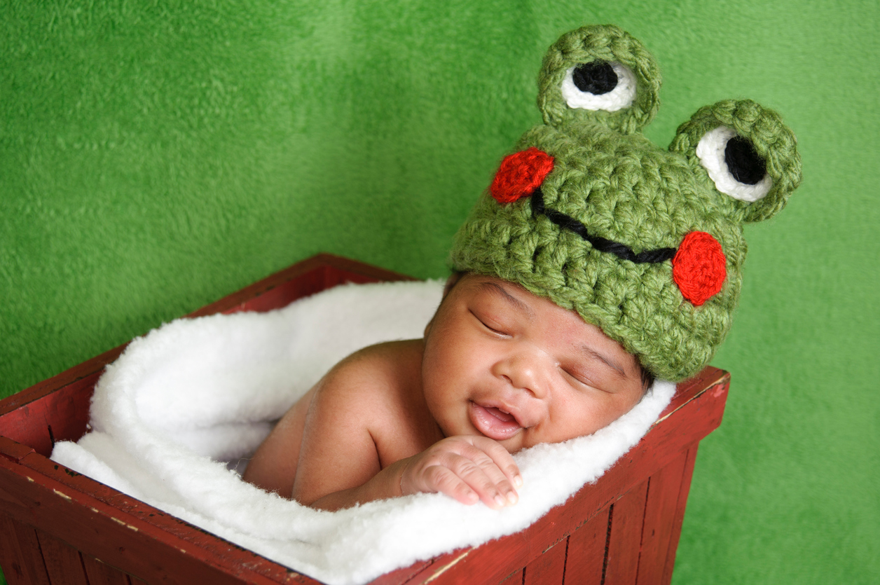 Smiling Newborn Wearing a Frog Hat