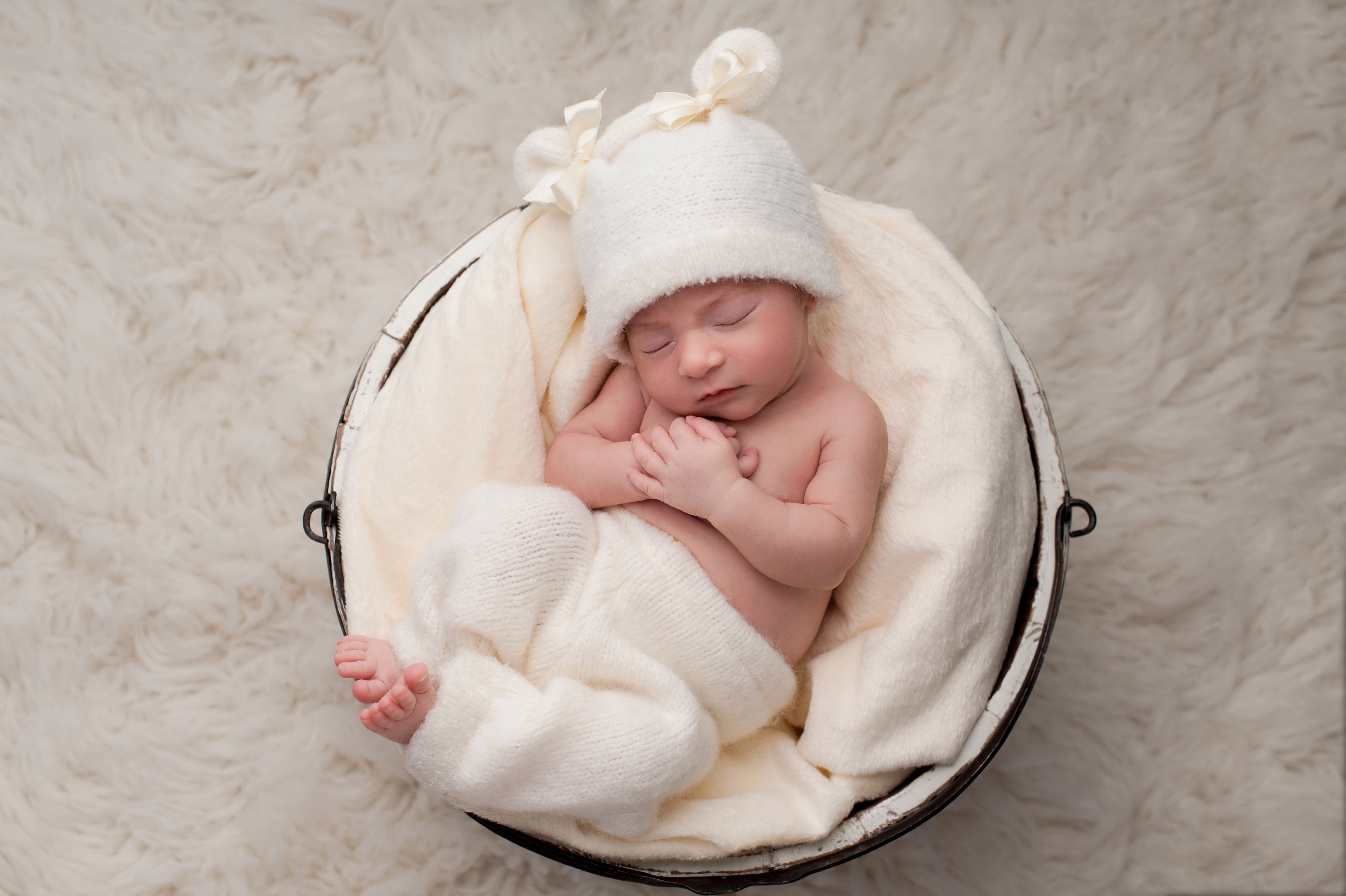 A sleeping nine day old newborn baby girl sleeping in a white wooden bucket. She is wearing upcycled pants and a matching hat.