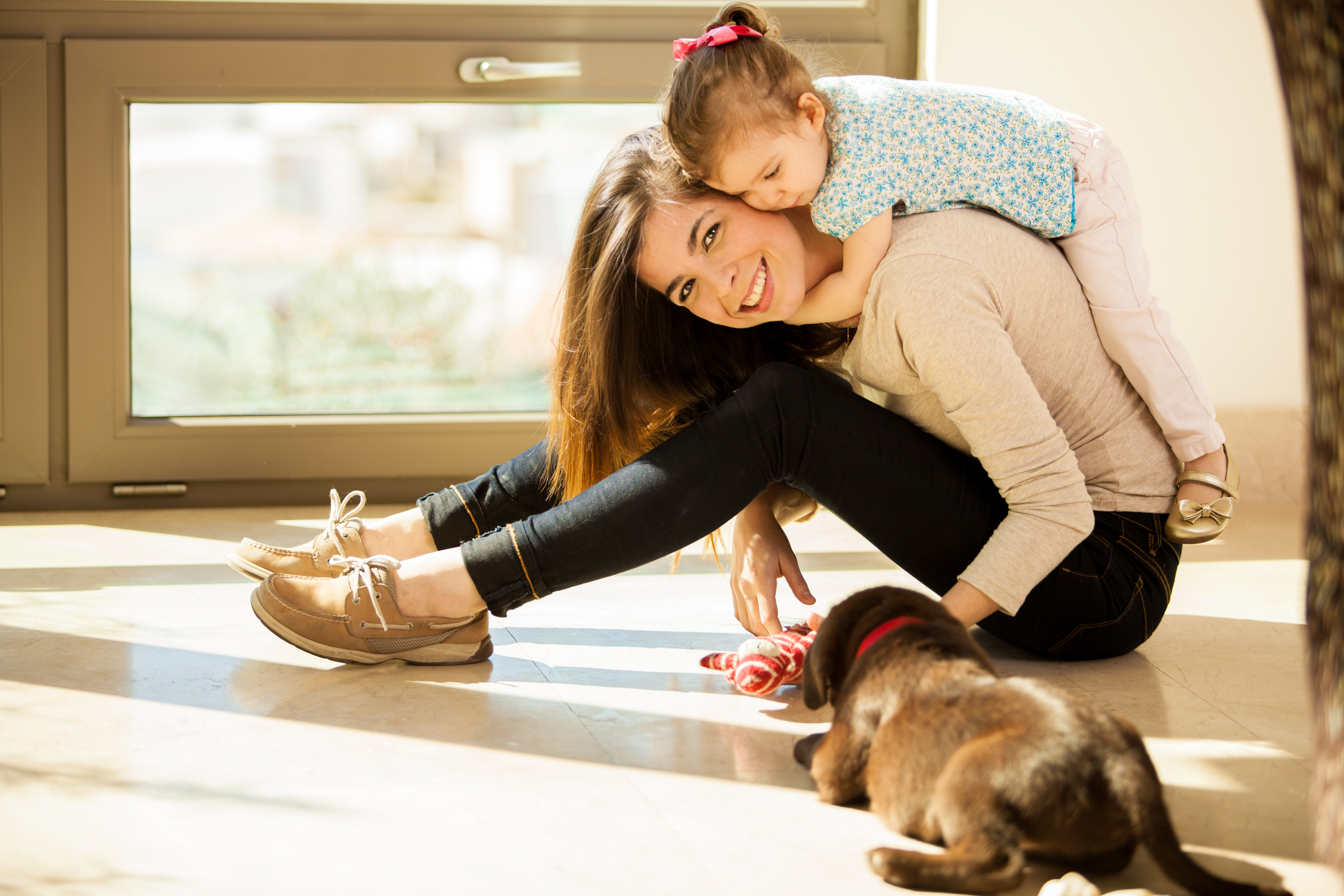 Beautiful young Hispanic mother with a baby girl and a cute Labrador puppy at home
