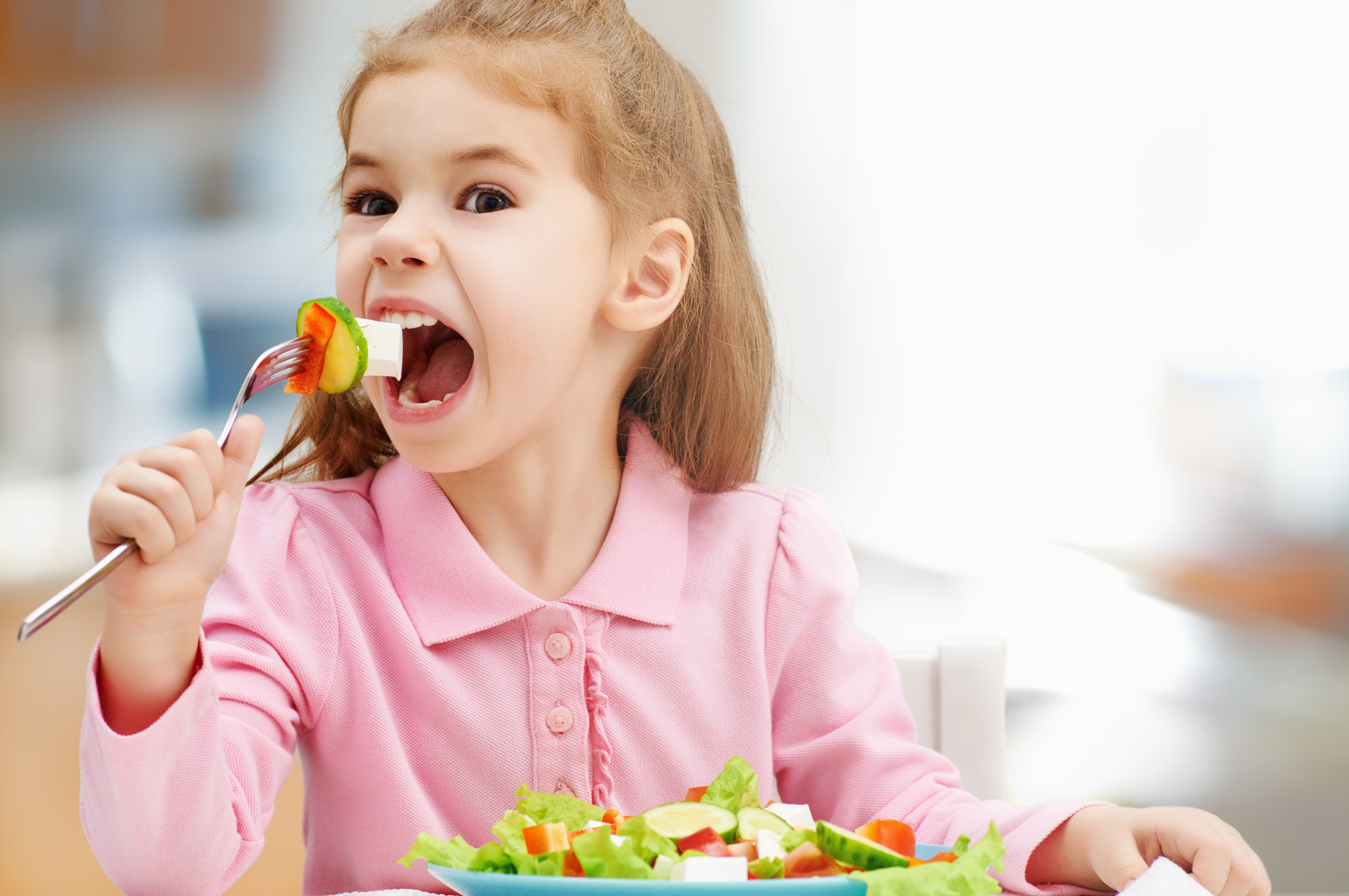 little girl eating a fresh salad