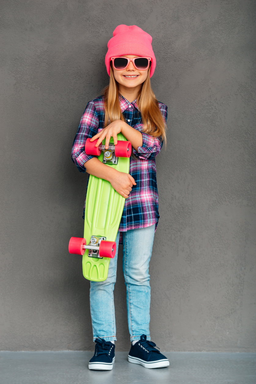 Full length of cheerful little girl in sunglasses looking at camera with smile and holding skateboard while standingagainst grey background