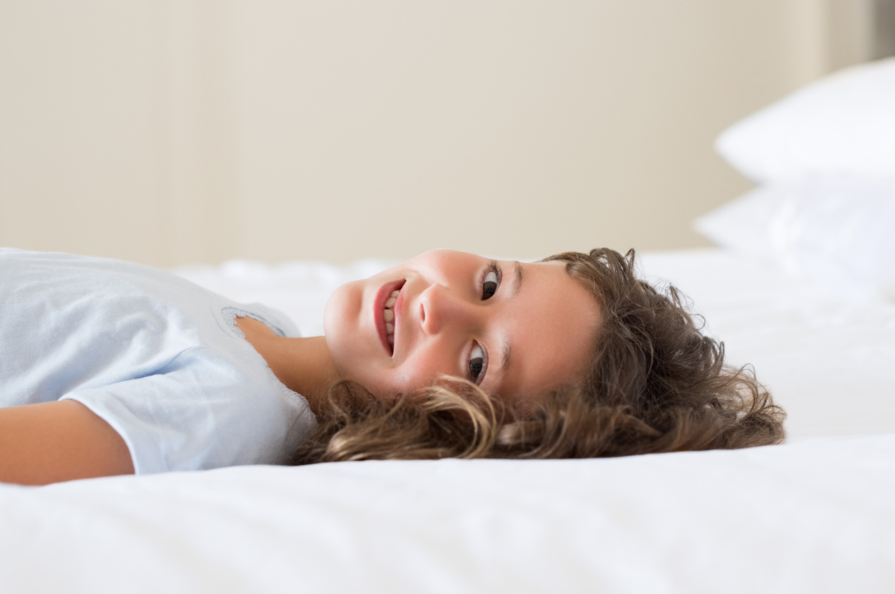 Pretty child lying down on white bed. Cute smiling little girl in her bed. Happy child relaxing at bed and looking camera.