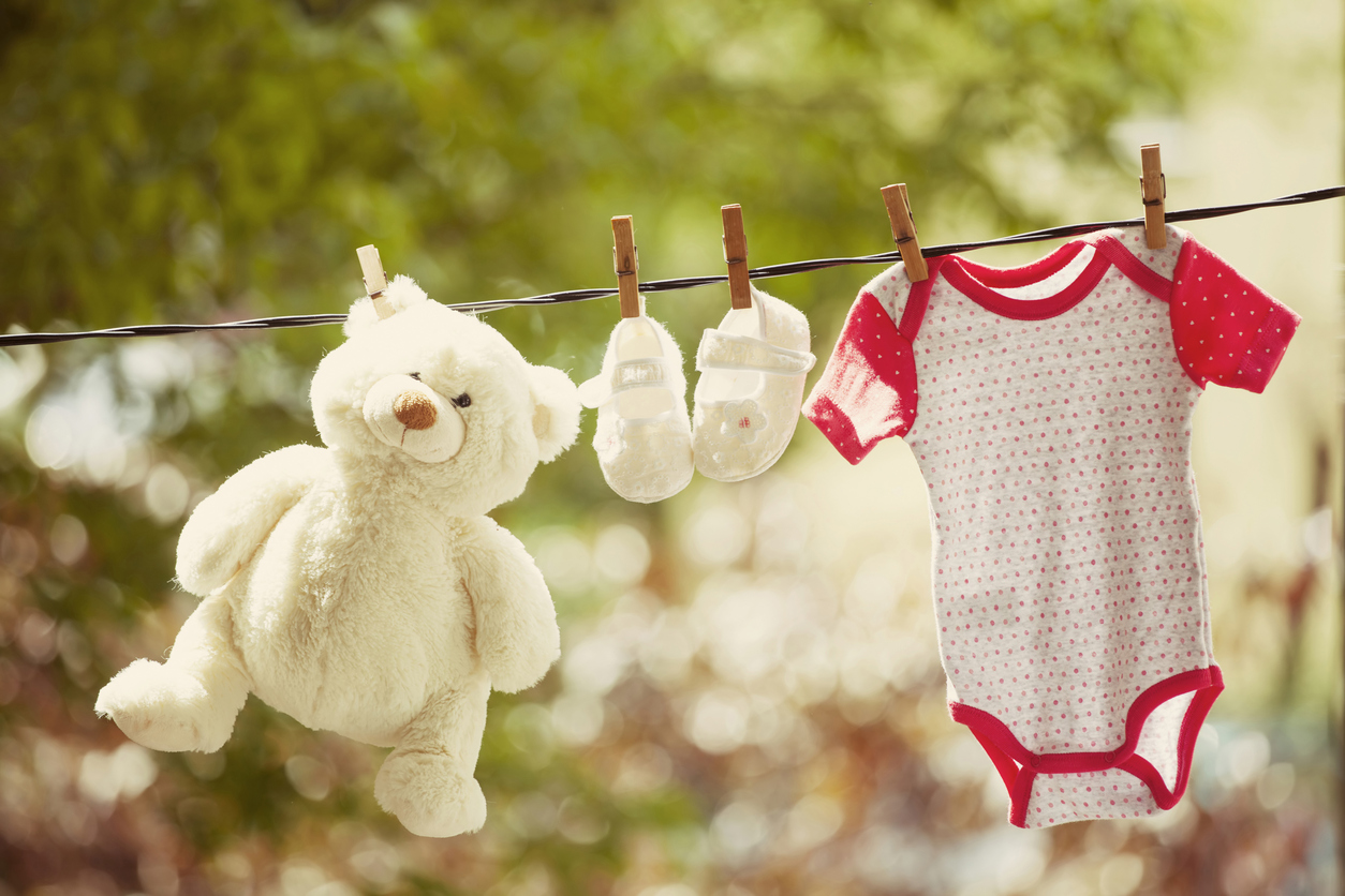 Baby clothes and teddy bear hanging on the clothesline - family concept