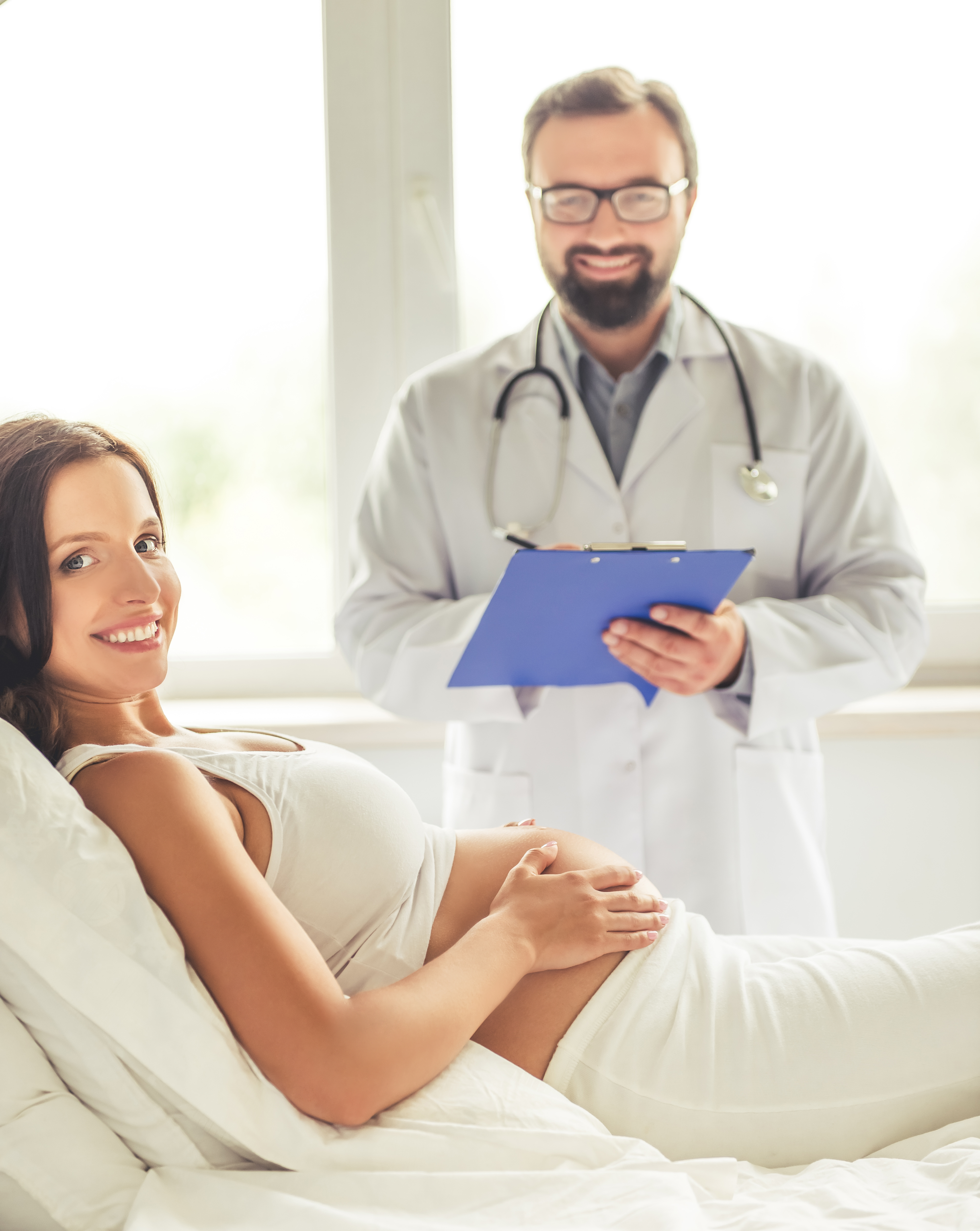 Beautiful pregnant young woman is touching her bare tummy while a handsome doctor is making notes. Both are looking at camera and smiling