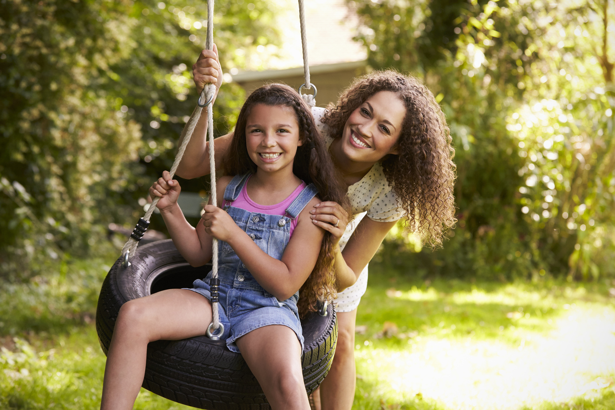 Mother Pushing Daughter On Tire Swing In Garden
