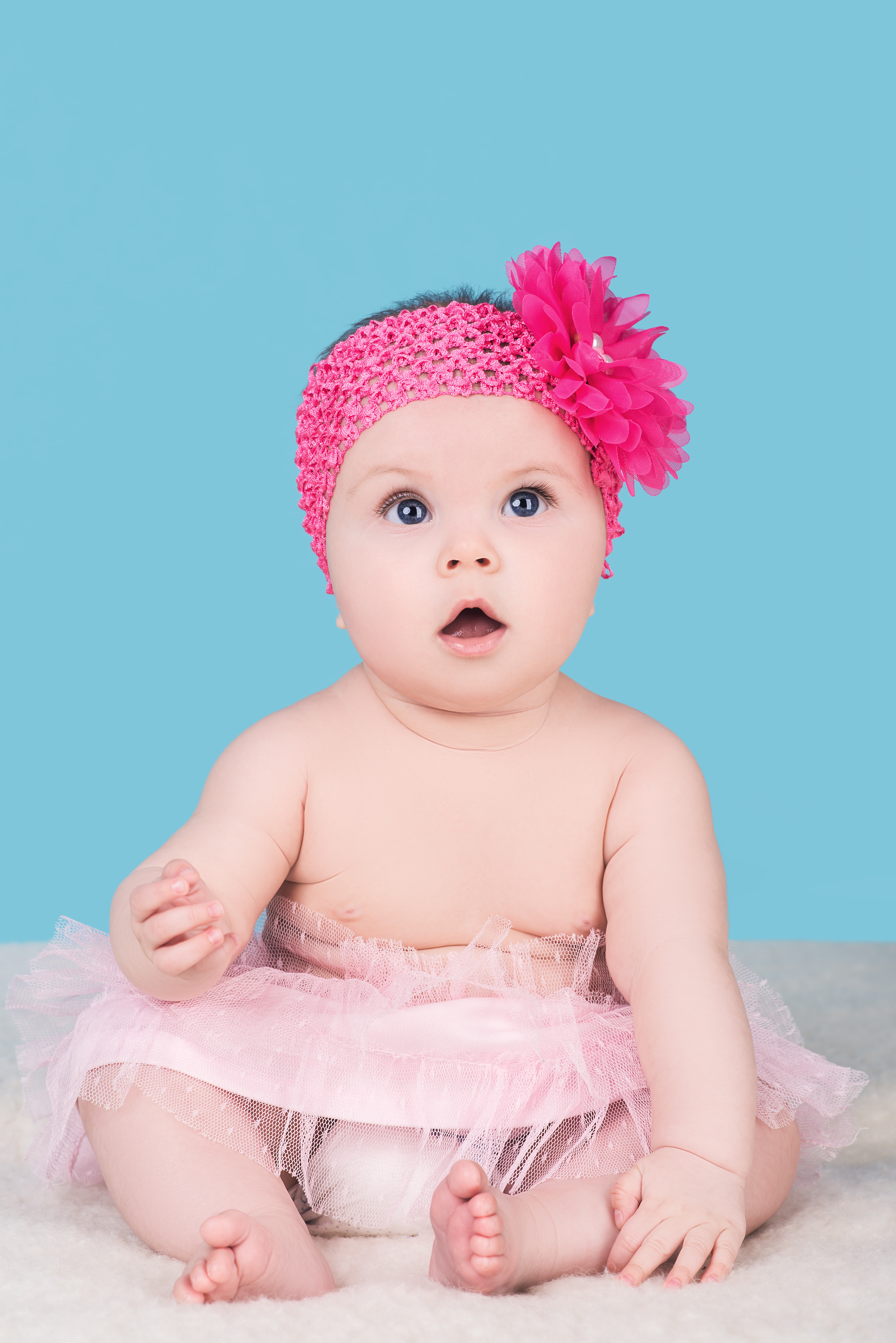 cute baby girl with pink bow flower on her head, isolated on blue. surprised child with big blue eyes look away