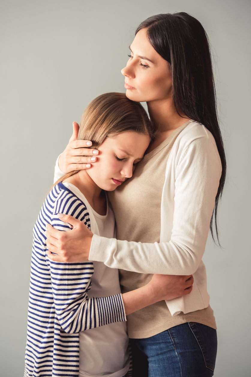Beautiful young mom is hugging her teenage girl, on gray background