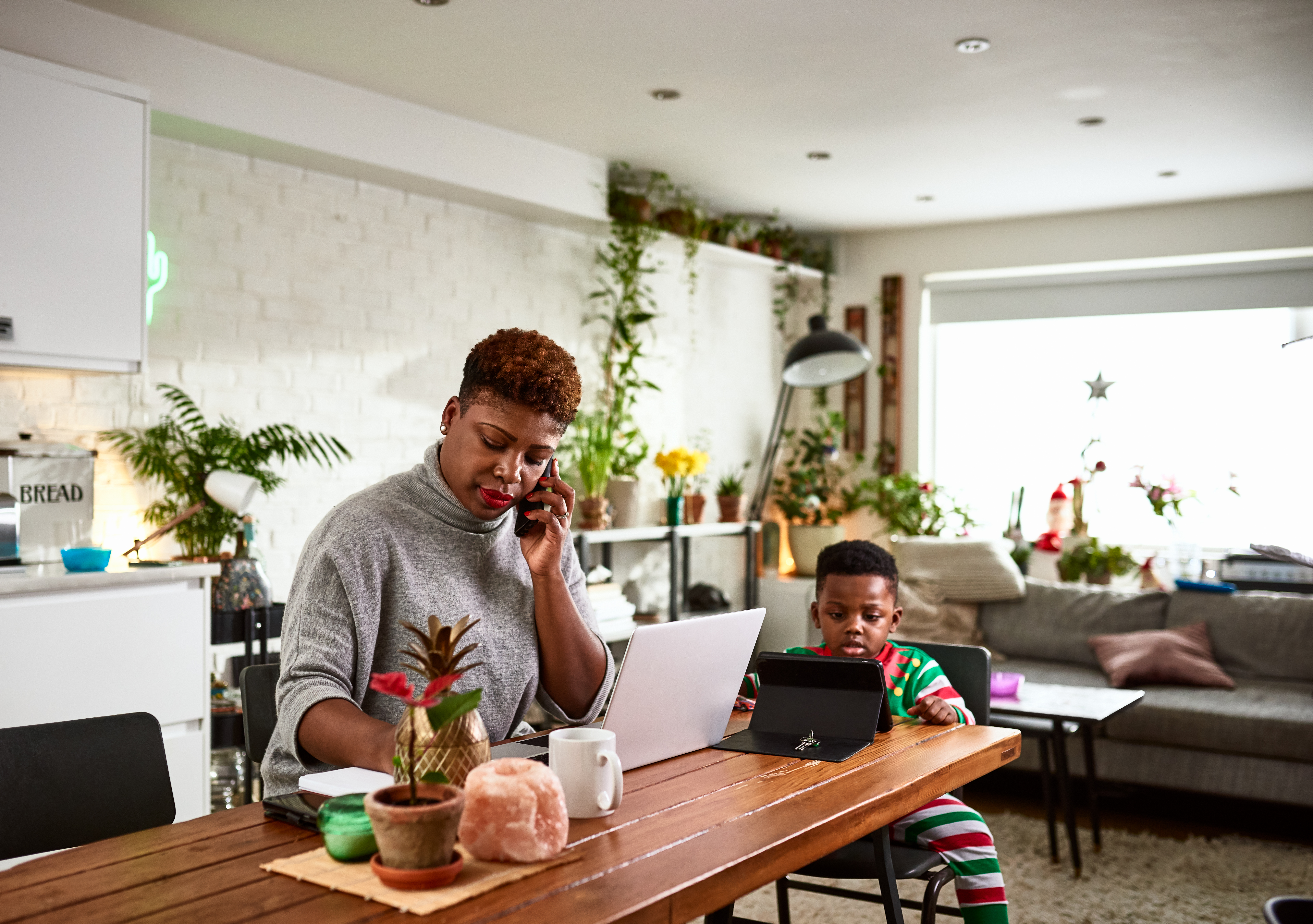 Multi tasking mother looking after son and working from home, modern parenting, freelancer, responsibility